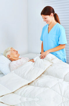 caregiver and elder woman smiling to each other