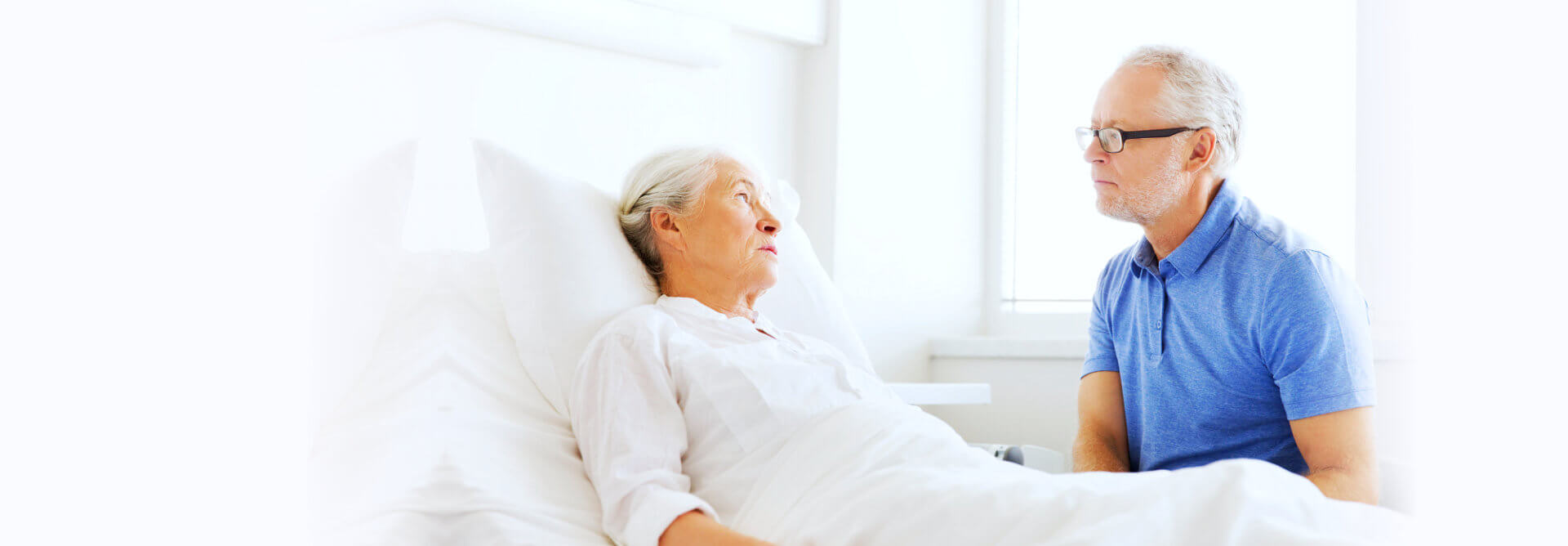 elder woman lying on bed while looking to her husband