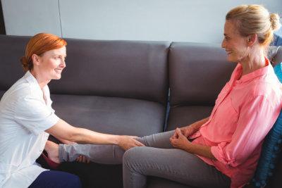 Nurse giving leg massage to senior women in a retirement home